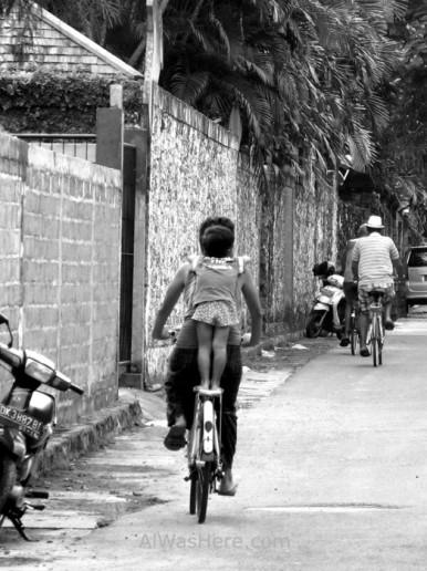 Un balinés con su hija y una pareja de turistas en bicicleta