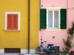 Moto frente a casas de colores en Gargnano, Italia