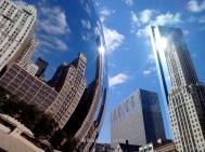 La famosa escultura Puerta de la Nube (Cloud Gate) en el Millennium Park reflejando edificios cercanos