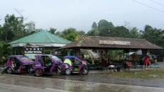 Triciclos morados junto al cruce de la carretera principal en Salvación, y gente esperando en la parada de minivans, autobús y jeepney resguardándose de la lluvia en otra parada intermedia en nuestro trayecto El Nido - Sabang donde Lexus Shuttle obliga a cambiar de furgoneta