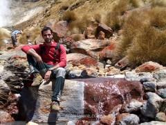 El mineral de hierro del agua tizna las rocas de rojo, como ocurre en Río Tinto, en España. Detrás mía otros escursionistas relajan sus pies en el agua y más a la izquierda se puede ver el humo de una fumarola