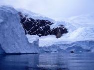 El glaciar se pierde de vista por encima de las montañas. En el agua se ve una de nuestras lanchas zodiac